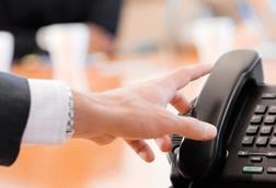 A hand reaching for the phone, in an office or meeting room
