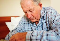 Elderly man, sitting on bed