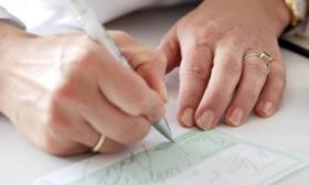 Woman's hands writing out a prescription