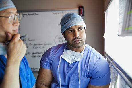 Hospital surgeons looking at X-ray