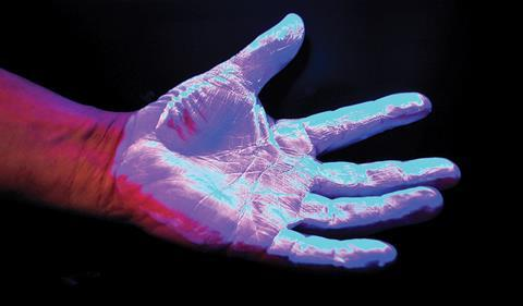 Hand hygiene: A hand under ultraviolet light to hightlight dirt