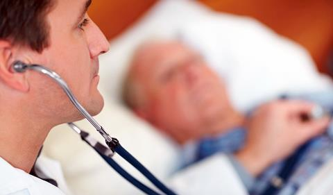 Old man in bed, doctor using stehoscope