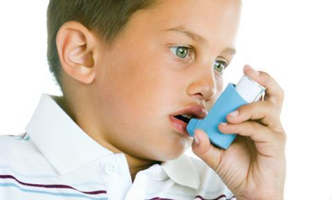Young boy using an inhaler for treatment of asthma