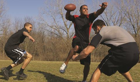 Men playing American football in park