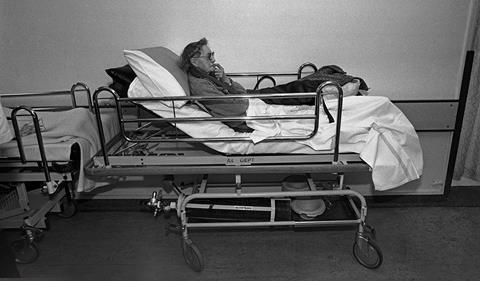 Elderly woman in a hospital trolley alone in a corridor