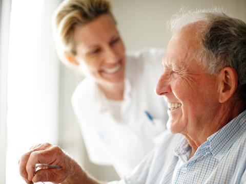 Elderly man in wheelchair with smiling healthcare worker